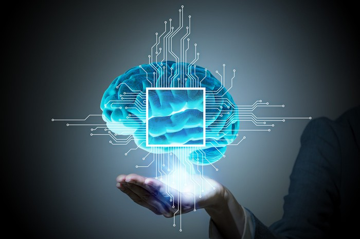A 3D rendering of a human brain floats above a businessperson's outstretched hand.