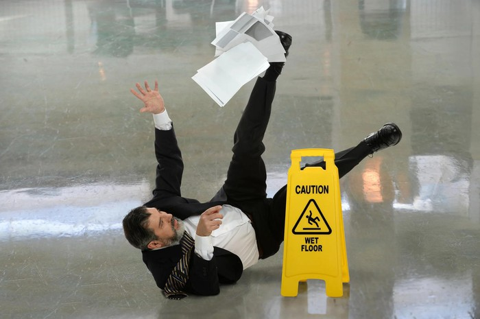 Man in suit falling down and spilling papers next to caution sign saying Wet Floor