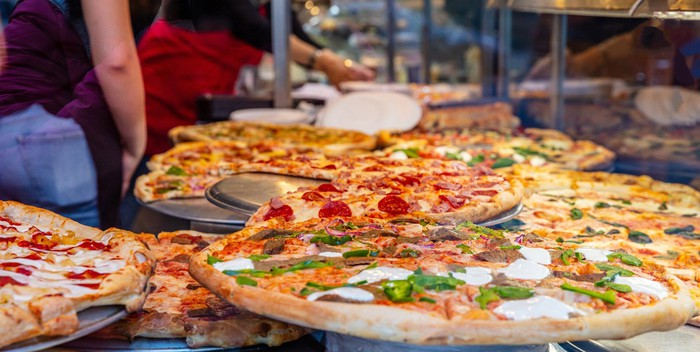Several large pizzas on serving platters.