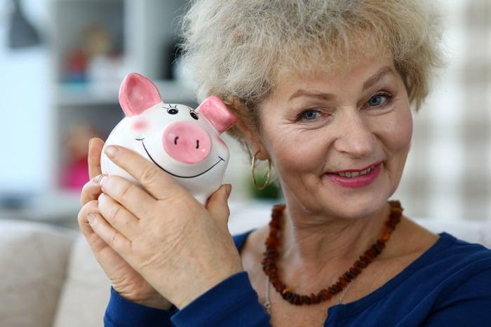 A woman holding up a piggy bank.