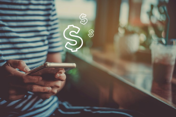 A person on their phone, presumably sending or receiving cash through an app as dollar signs are superimposed coming from the phone.