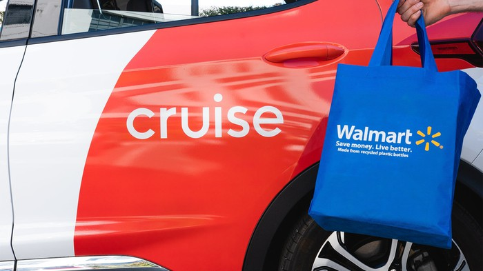 A blue Walmart shopping back next to a Cruise self-driving taxi.