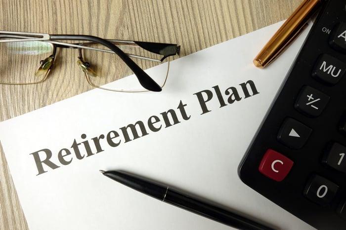 Written retirement plan lying on a desk, next to a calculator.