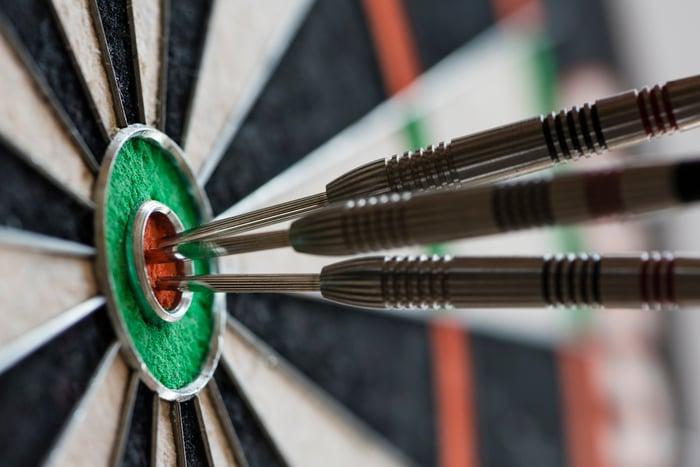 Three darts in the bullseye section of a dartboard.