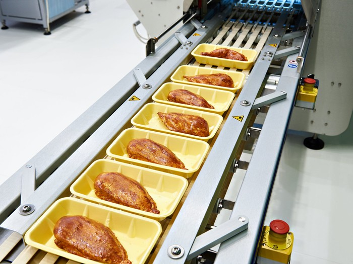 Chicken meat in yellow plastic foam packages on a conveyor, about to be shrink-wrapped by a machine.