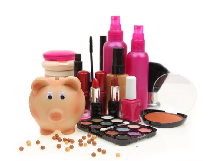 Lipstick and other makeup next to a piggy bank