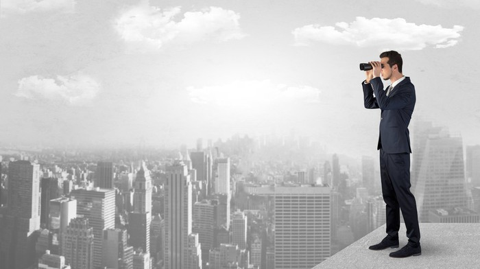 Rendering of a young businessperson surveying a grayscale city with binoculars from the top of a tall building.