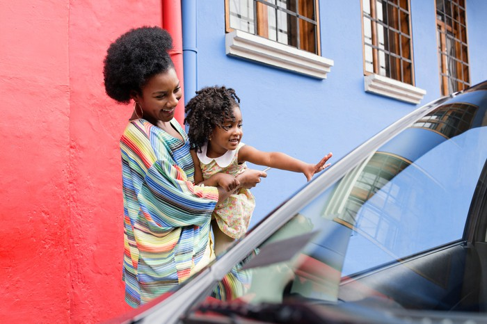 Woman holding child, who's waving to someone in a car.