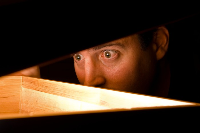A man peeks into a wooden box.