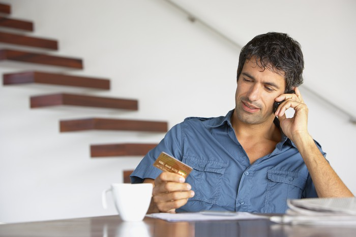 Man looking at a credit card as he holds a cell phone to his ear.