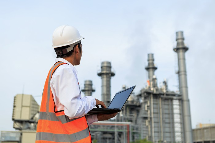 An engineer surveying an oil and gas refinery while holding an open laptop.