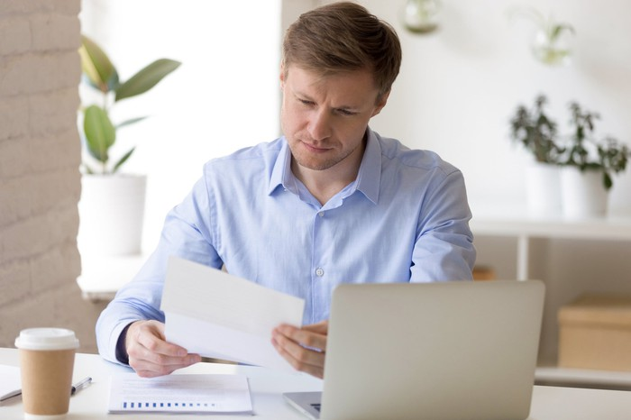 Man at laptop looking at document