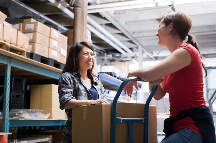 Two women chatting while loading a box onto a trolley in a warehouse.