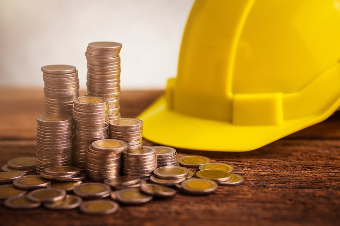 Stacks of coins next to a yellow hard hat on a wooden table