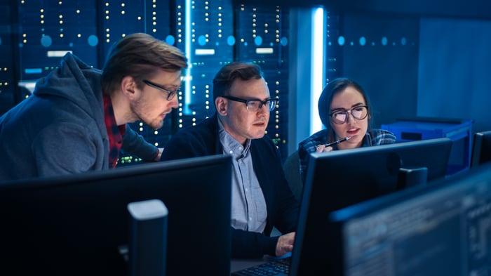 Three IT professionals work at a computer.