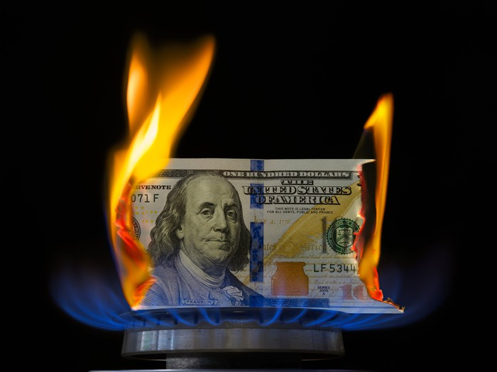 A one hundred dollar bill on fire atop a lit stove burner.