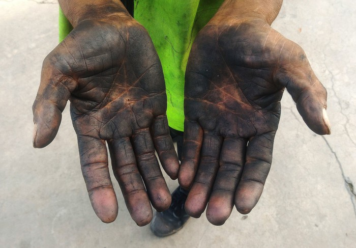 A pair of hands stained with oil.