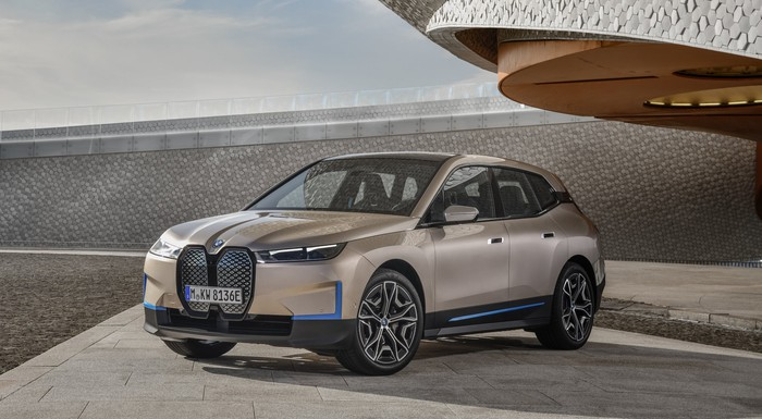 A pale gold BMW iX, an edgy-looking electric luxury SUV.