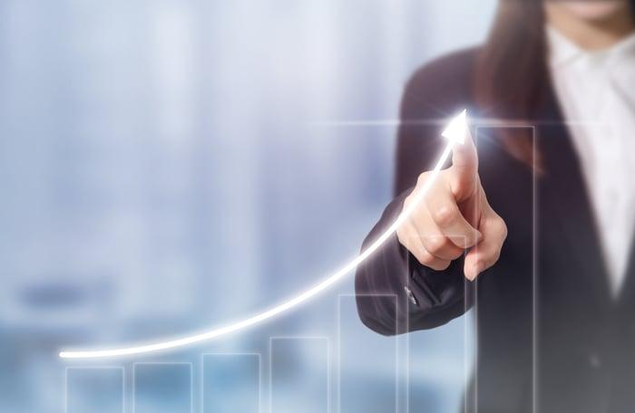 A businesswoman draws an upward arrow on a bar chart displayed on a transparent touchscreen.