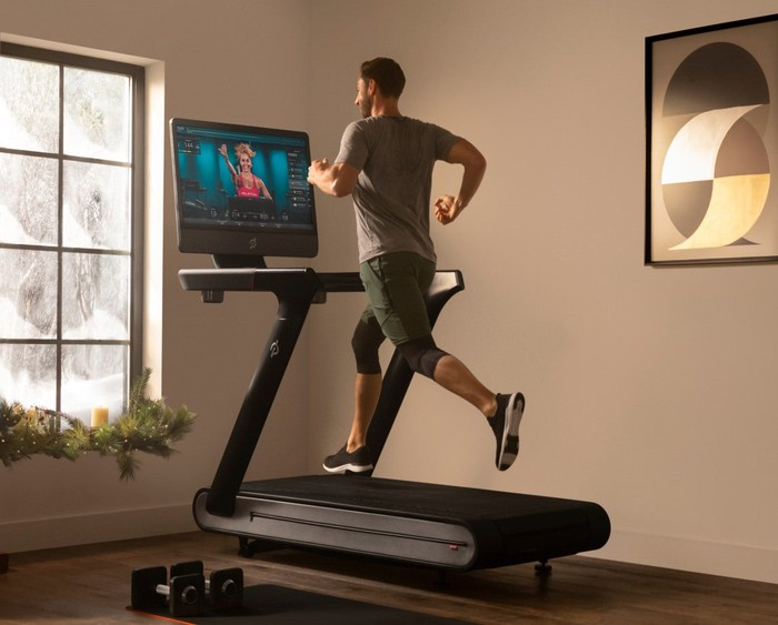 Man running on a treadmill while watching a fitness instructor on a screen