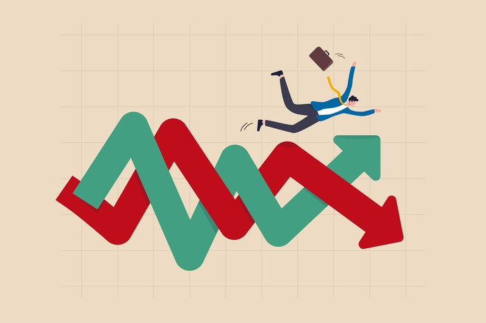 A green line and a red line intertwined as they rise and fall, an investor falling over.