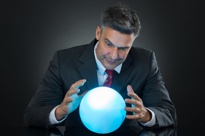Man in a suit staring at a crystal ball that is hovering between his hands.