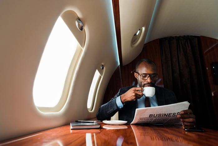 Man sitting near plane window reading newspaper and drinking coffee