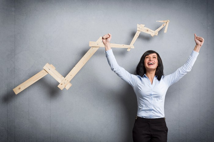 A cheering businesswoman standing in front of a choppy but rising wooden chart.