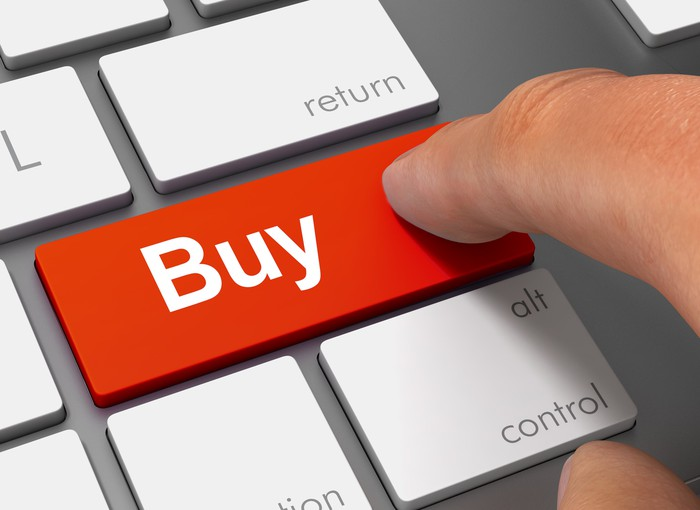 """An investor's finger touches a """"buy"""" key on a keyboard."""