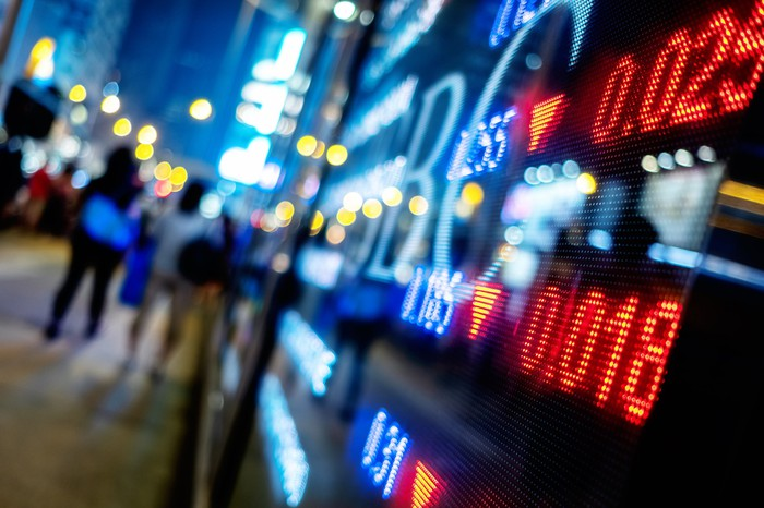Stock tickers in a window at night.