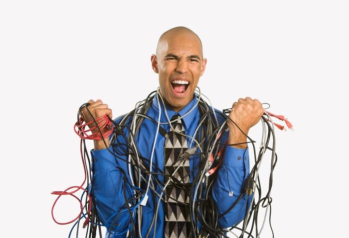An angry businessman is wrapped in many different computer cables, clutching them by the handful.