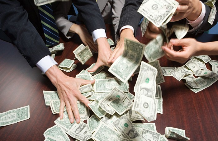 People in business suits grabbing piles of money off table.