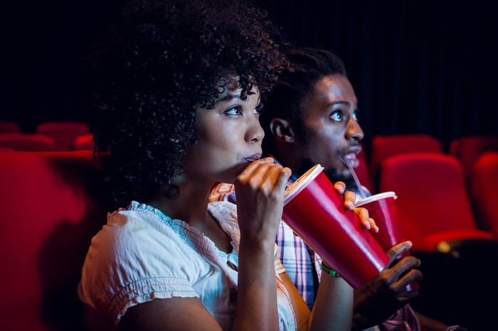 Two people drinking sodas in a movie theater.