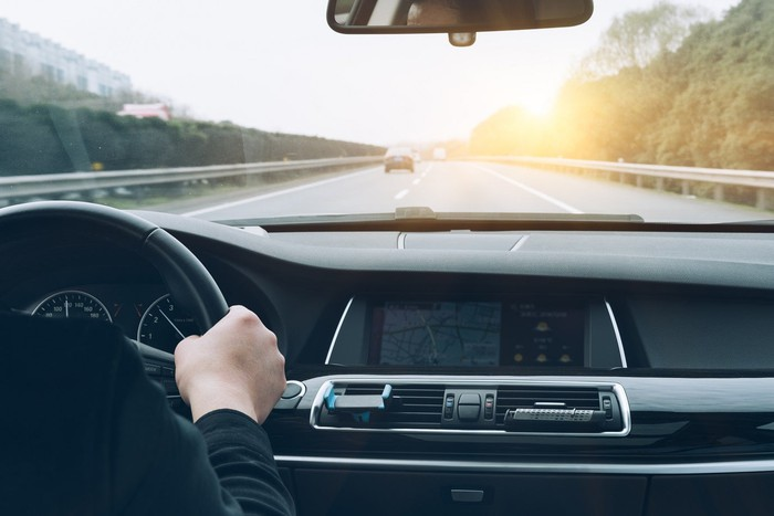 View of car dashboard on a road, with light traffic ahead and a rising or setting sun.