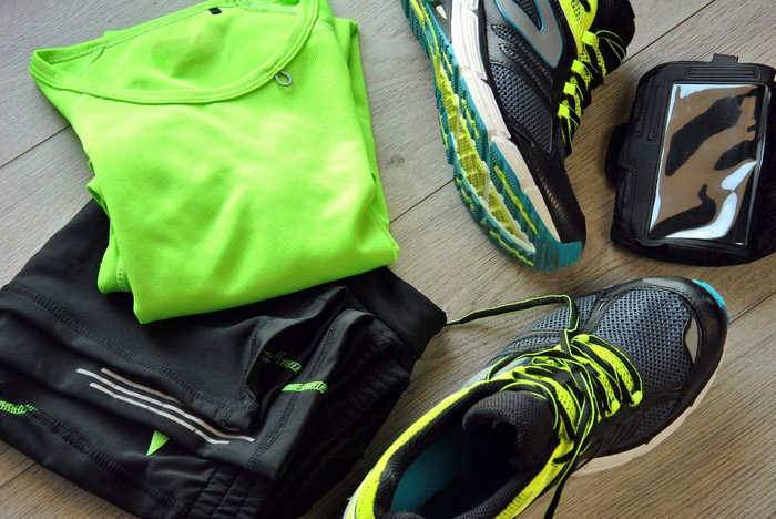 Athletic clothing and shoes laying on a floor.