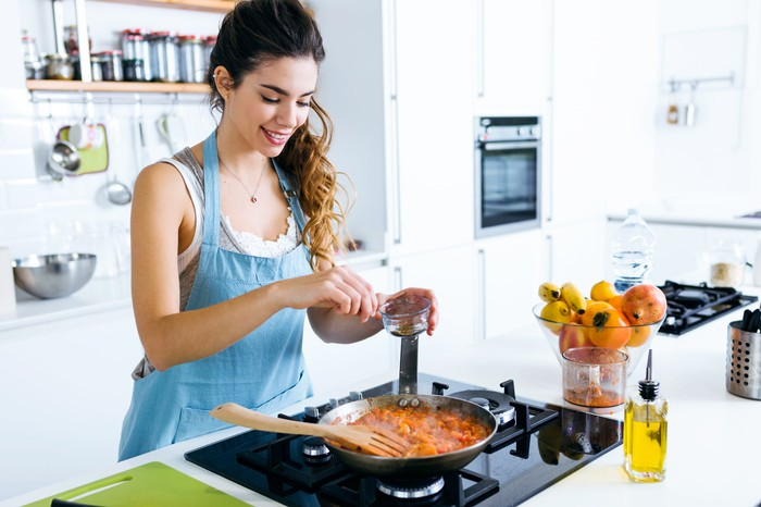 A young woman cooking at home.