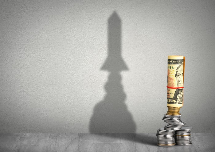A roll of dollar bills stands on several coin stacks, casting a rocket-shaped shadow on the wall.