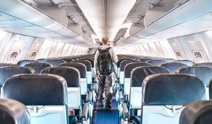 Passenger walking through a nearly empty plane cabin.