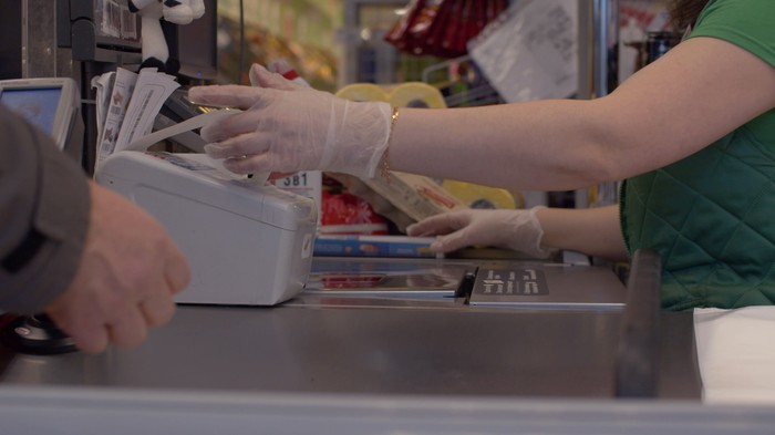 Grocery store cashier working a checkout.