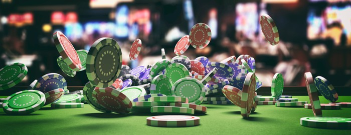 Poker chips on a green card table in a casino.