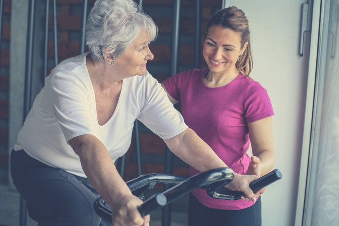 Old lady on exercise bike while younger lady smiles and looks on