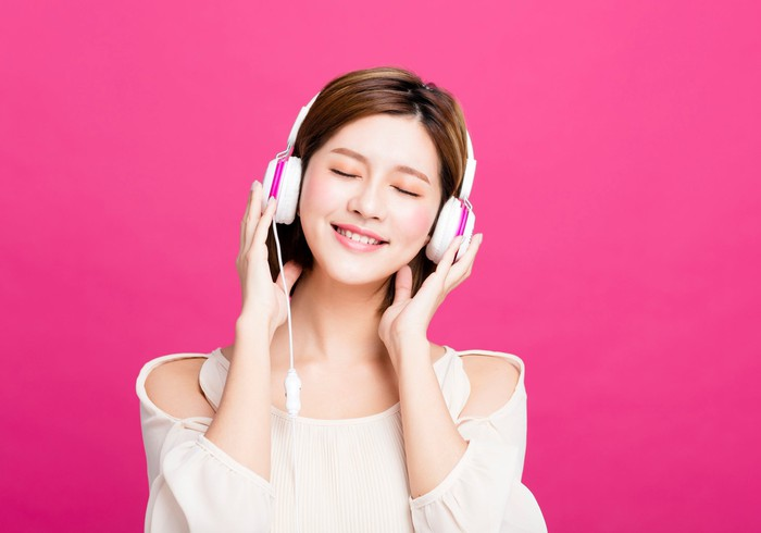A woman listens to music on her headphones.