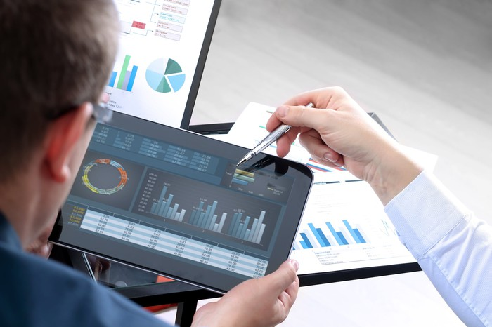 A person looking at charts on a tablet.