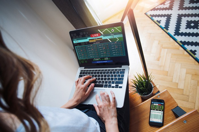 woman sports betting online with laptop and smartphone