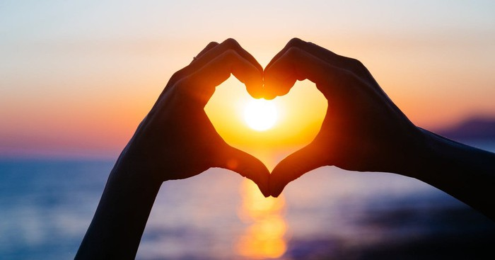 Two hands forming heart, with sun shining through.