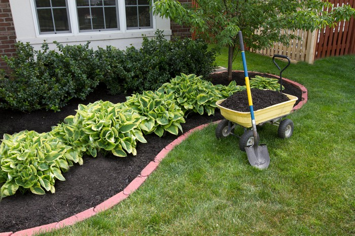 Landscaping tools in front of small garden