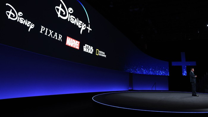 A large screen showing the logos for Disney+ and other content brands during a company presentation.