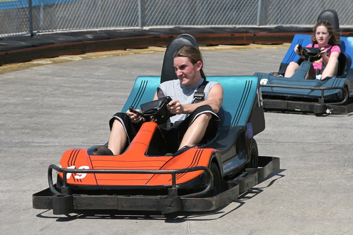 Two electric bumper cars race around a track.