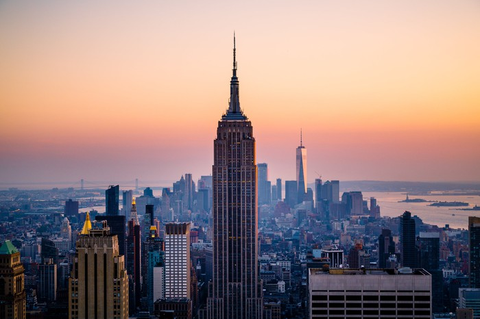 Empire State Building in panoramic view of New York City at sunset.