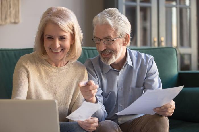Smiling older man and woman at laptop